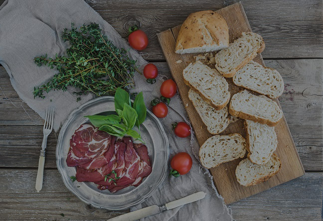 Smoked meat in vintage silver plate with fresh basil, cherry-tomatoes and bread slices over rustic wood backdrop. Top view